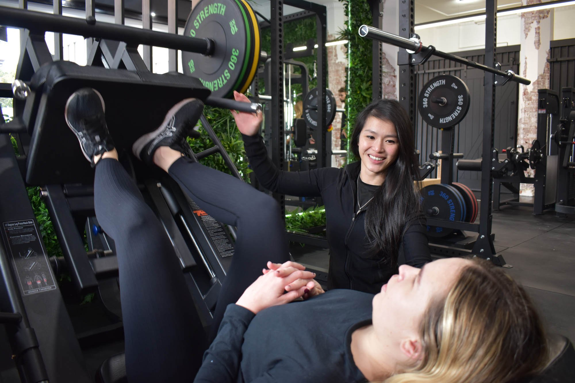 Physiotherapist working on a specialised training program with customer doing leg squat.